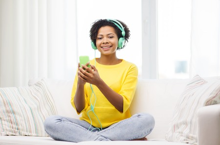 personas escuchando: las personas, la tecnolog�a y el concepto de ocio - feliz africano americano joven mujer sentada en el sof� con el tel�fono inteligente y auriculares escuchando m�sica en casa