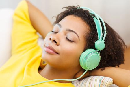 mensen, technologie en vrije tijd concept - Gelukkig Afro-Amerikaanse jonge vrouw, zittend op de sofa met een koptelefoon luisteren naar muziek in huis Stockfoto