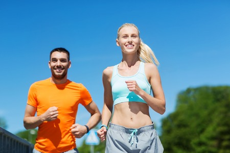people: fitness, sport, friendship and healthy lifestyle concept - smiling couple running outdoors Stock Photo