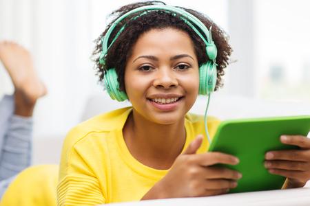 mujeres negras: las personas, la tecnología y el concepto de ocio - feliz mujer joven del afroamericano que miente en el sofá con tablet pc ordenador y los auriculares escuchando música en casa