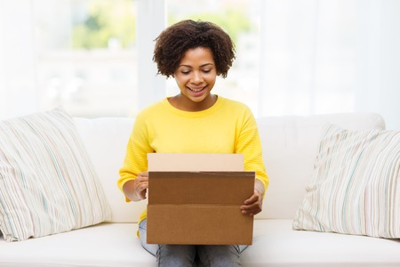 woman on couch: people, delivery, shipping and postal service concept - happy african american young woman opening cardboard box or parcel at home Stock Photo