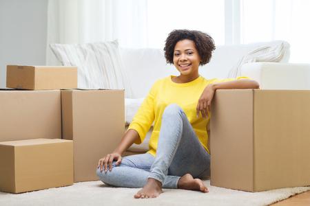 mensen, het verplaatsen nieuwe plaats en reparatie concept - Gelukkig Afro-Amerikaanse jonge vrouw met vele kartonnen dozen zitten op de vloer thuis