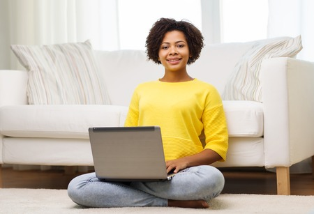 people, technology and leisure concept - happy african american young woman sitting on floor with laptop computer at home Stockfoto