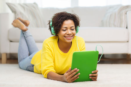 cheerful teen girl: people, technology and leisure concept - happy african american young woman lying on floor with tablet pc computer and headphones listening to music at home