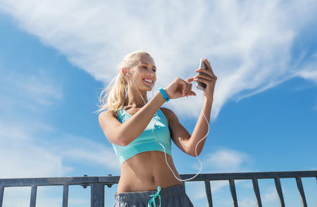 people listening: fitness, sport, people, technology and healthy lifestyle concept - smiling young woman with smartphone and earphones listening to music and exercising outdoors Stock Photo