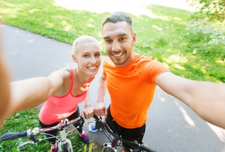 riding: fitness, sport, people, technology and healthy lifestyle concept - happy couple with bicycle taking selfie outdoors