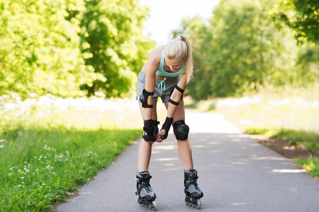 protective: fitness, sport, summer, rollerskating and healthy lifestyle concept - happy young woman in rollerskates and protective gear riding outdoors Stock Photo