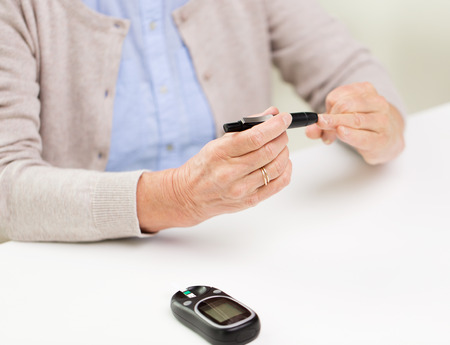 glucometer: medicine, age, diabetes, health care and people concept - close up of senior woman with glucometer checking blood sugar level at home