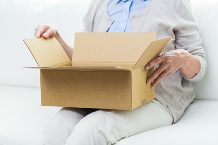 mail: age, delivery, mail, shipping and people concept - close up of senior woman looking into open parcel box at home