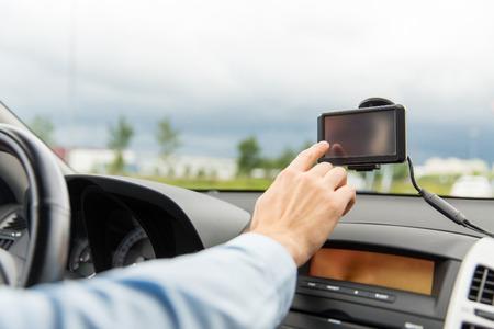 교통, 비즈니스 여행, 기술, 탐색 및 사람들 개념 - 가까운 남성의 손에 GPS를 네비게이터를 사용하여 최대 운전하는 차를 운전하는 동안 스톡 콘텐츠