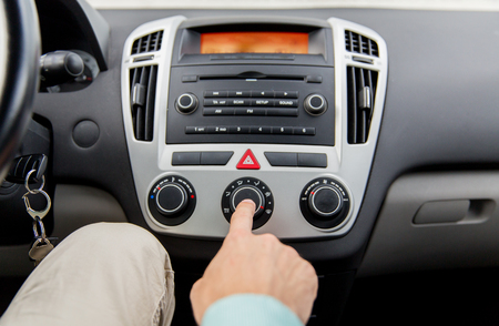 regulating: transport, road trip, car driving, technology and people concept - close up of male hand using climate control in car