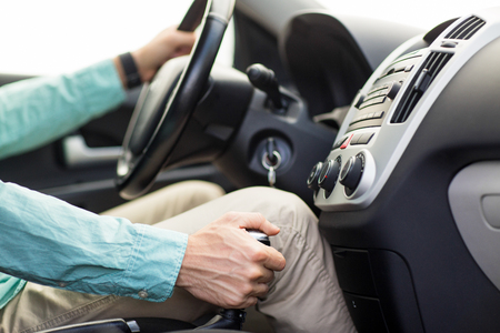 transmission: transport, business trip, speed, destination and people concept - close up of young man driving car