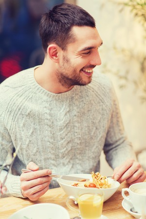 healthy men: people, leisure, eating and food concept - happy young man having dinner at restaurant, cafe or home Stock Photo
