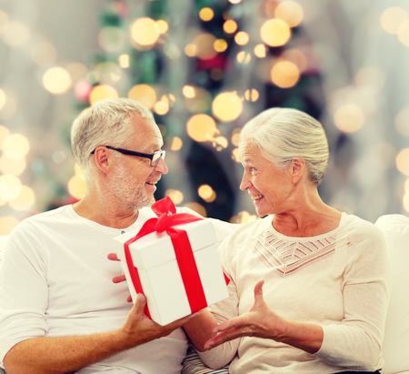 surprise gift: family, holidays, age and people concept - happy senior couple with gift box over christmas tree lights background