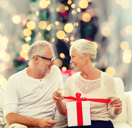lovely couple: family, holidays, age and people concept - happy senior couple with gift box over christmas tree lights background