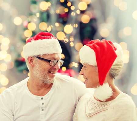 happy senior couple: family, holidays, age and people concept - happy senior couple in santa helper hats sitting on sofa over christmas tree lights background