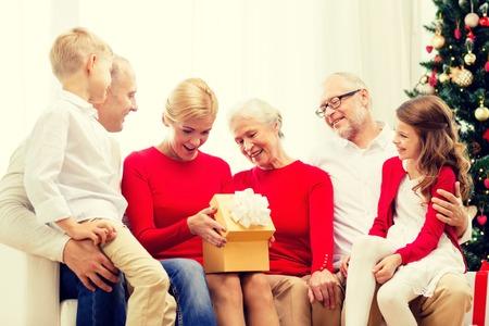 abuelos: familia, días de fiesta, la generación, el concepto de Navidad y la gente - sonriendo familia con cajas de regalo sentado en el sofá en casa