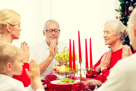 familia orando: family, holidays, generation, christmas and people concept - smiling family having dinner and praying at home
