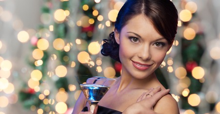 party, drinks, holidays, luxury and celebration concept - woman face with cocktail over christmas tree lights