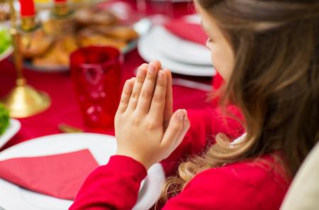 family praying: familia, día de fiesta, la religión, la tradición y el concepto de la gente - cerca de niña rezando en la cena de Navidad en casa