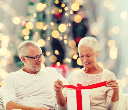grandfather and grandmother: family, holidays, age and people concept - happy senior couple with gift box over christmas tree lights background