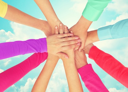 homosexual sex: people, gesture, gay pride and homosexual concept - close up of women hands in rainbow clothes on top of each other over blue sky background