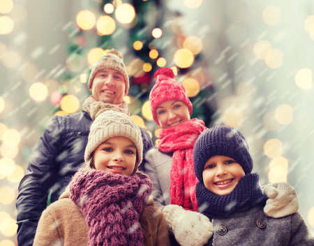 background lights: family, childhood, season, holidays and people concept - happy family in winter clothes over christmas tree lights background
