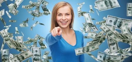 pieniądze: biznes, pieniądze, finanse, ludzie i gest koncepcja - uśmiechnięta kobieta z pieniędzy dolara pieniężnych wskazując palcem na Ciebie na niebieskim tle