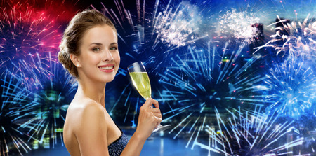 celebrating: party, drinks, holidays, luxury and celebration concept - smiling woman in evening dress with glass of sparkling wine over nigh city and firework background