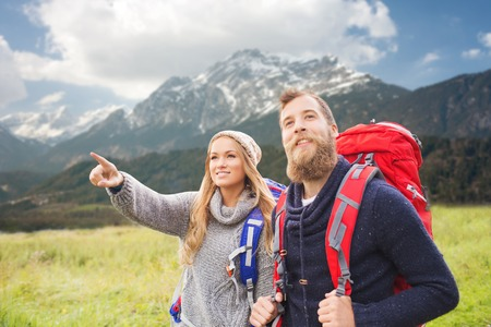 adventure, travel, tourism, hike and people concept - smiling couple walking with backpacks and pointing finger to something over mountains background Imagens