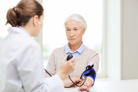 hypotension: medicine, age, health care and people concept - doctor with tonometer checking senior woman blood pressure level at hospital