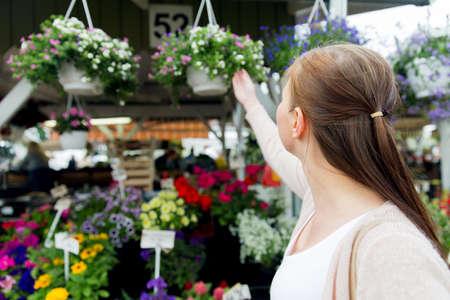 mujeres de espalda: venta, compras, jardinería y concepto de la gente - cerca de la mujer la elección de las flores en el mercado de la calle Foto de archivo