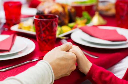 family praying: concepto de familia, de vacaciones, la tradición, la generación y la gente - cerca de la familia que tiene la cena de navidad y de la mano en el hogar