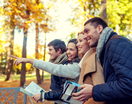 touristic: travel, people, tourism, gesture and friendship concept - group of smiling friends with map standing on bridge and pointing finger in city park