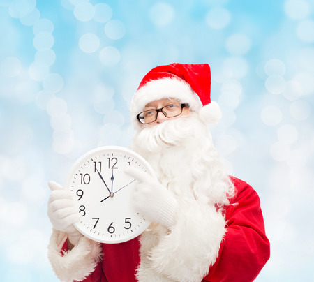 reminding: christmas, holidays and people concept - man in costume of santa claus with clock showing twelve over blue lights background Stock Photo