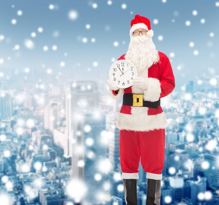 twelve month old: christmas, holidays and people concept - man in costume of santa claus with clock showing twelve over snowy city background