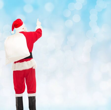 christmas red: christmas, holidays and people concept - man in costume of santa claus with bag pointing finger from back over yellow lights background over blue lights background
