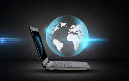 internet globe: technology, business, mass media and internet concept - open laptop computer with globe projection over dark gray background