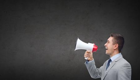 het bedrijfsleven, mensen, communicatie en publieke aankondiging concept - gelukkig zakenman in pak spreken tot megafoon over donkere grijze betonnen muur achtergrond