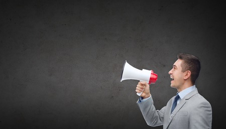 Unternehmen, Menschen, Kommunikation und öffentliche Ankündigung Konzept - glücklich Geschäftsmann im Anzug zu sprechen über dunkelgrauen Betonwand Hintergrund Megaphon Standard-Bild