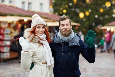 lifestyle outdoors: holidays, winter, christmas, gesture and people concept - happy couple of tourists in warm clothes waving hands in old town Stock Photo