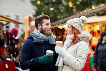 and in winter: holidays, winter, christmas, hot drinks and people concept - happy couple of tourists in warm clothes drinking coffee from disposable paper cups in old town