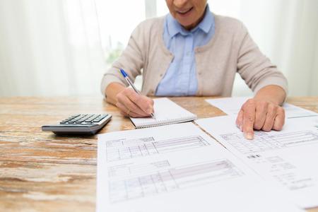 비즈니스, 저축, 연금 보험, 연령 및 사람들이 개념 - 논문 또는 법안 및 집에서 작성하는 계산기와 수석 여자의가 까이 서