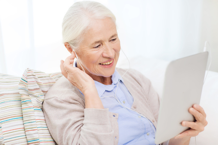 technology, age and people concept - happy senior woman with tablet pc computer and earphones listening to music at home