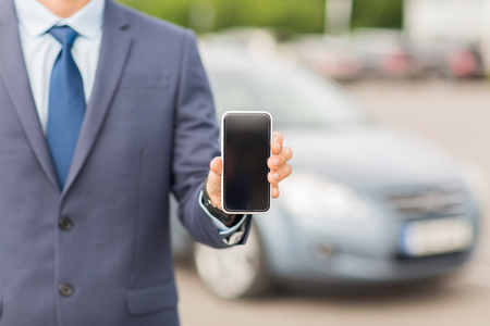 parking spaces: transport, business trip, technology and people concept - close up of man showing smartphone blank screen on car parking
