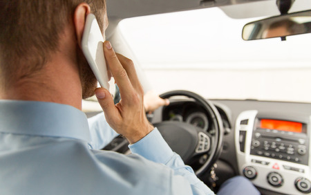 distraction: transport, business trip, technology and people concept - close up of young man with smartphone driving car
