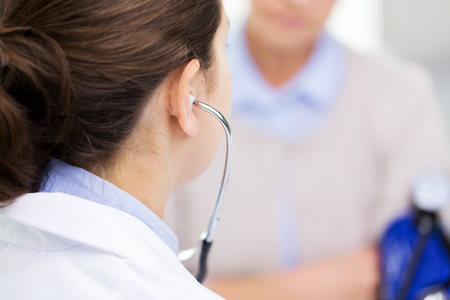 hypotension: medicine, age, health care and people concept - close up of doctor with tonometer checking senior woman blood pressure level at hospital