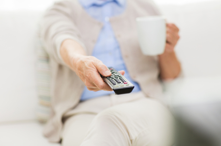 changing channels: technology, television, age and people concept - close up of senior woman watching tv, drinking tea and changing channels by remote control at home