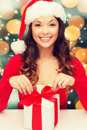 christmas woman: christmas, x-mas, winter, happiness concept - smiling woman in santa helper hat with gift box