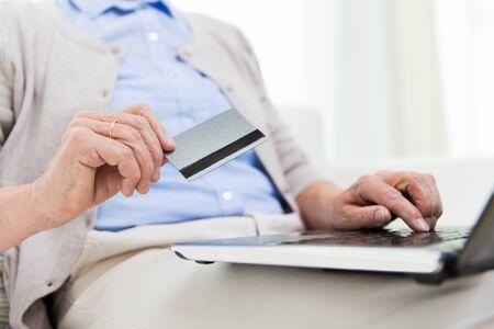 damas antiguas: la tecnolog�a, la edad y el concepto de la gente - cerca de la mujer mayor con calcular port�til y tarjeta de cr�dito o un banco en el pa�s r